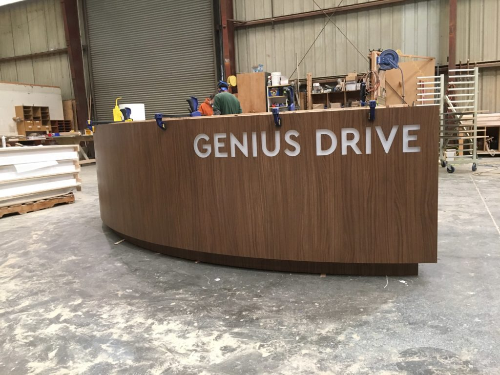 WoodLab Designs Crestmark Collaboration custom wood veneer letter laser cutout curved bar construction