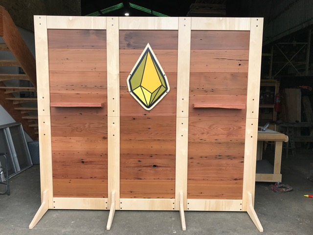WoodLab Designs Gold Nugget Ghee Eight foot Tall Trade Show Booth Wall made from upcycled Redwood Boards and deconstructs to fit on a single pallet